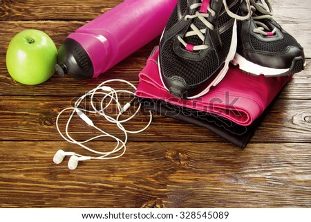 shoes, clothes, a bottle and headphones on a wooden background - stock photo