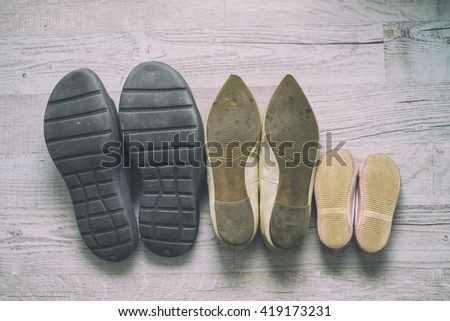 Shoes family/Image of a row of pairs of worn shoes, soles up, fit for a man, woman and child. - stock photo
