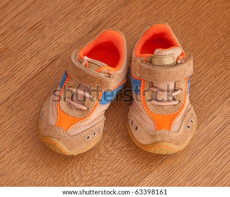 Shoes for Baby - Cross - on wooden floor ... - stock photo
