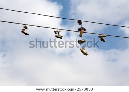 Shoes hanging from power lines are the stuff of urban legends - stock photo