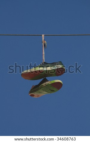 Shoes hanging on the wire - stock photo