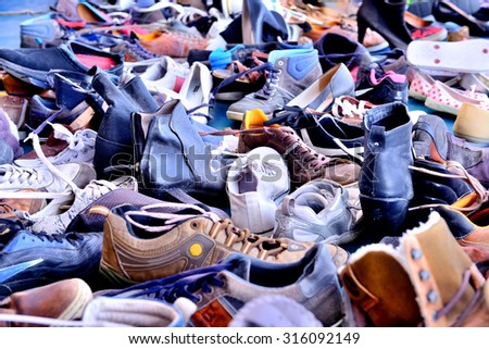 Shoes, lots of used in pile - stock photo