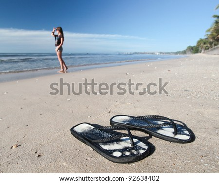 Shoes of woman on the beach and woman near sea - stock photo