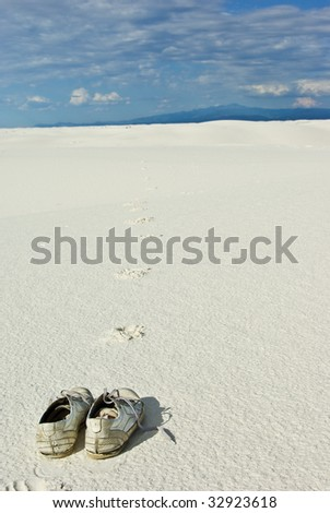Shoes on white sand leaving footprints