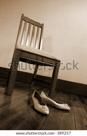 Shoes sit prepared for the days events in anticipation at the foot of a chair - stock photo