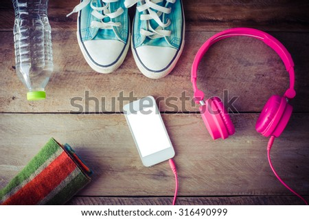 Shoes, water bottles headset smart phone scarf on a wooden table ready to depart.