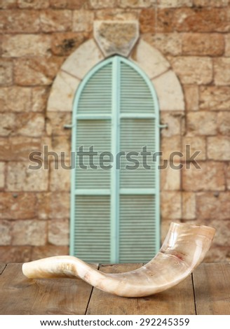 shofar (horn) on wooden table in front of jerusalem ancient window. rosh hashanah (jewish holiday) concept . traditional holiday symbol.  - stock photo