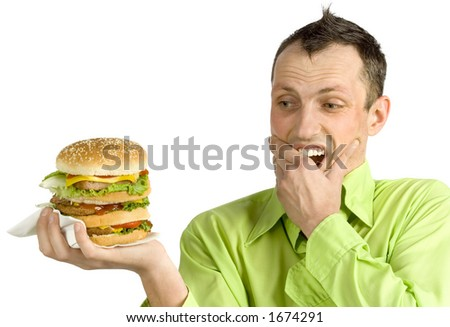 shoked man looks at huge hamburger - stock photo