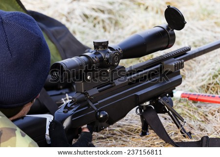 shooter aiming a rifle at a target - stock photo