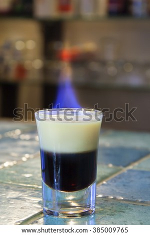 Shooter - B52 cocktail - layered and with the flame on the bar - table with blue ceramic tiles. - stock photo