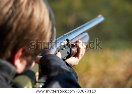 Shooter takes aim for a shot from rifle - stock photo