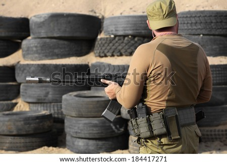 Shooter with a Kalashnikov assault rifle close to the rear view - stock photo