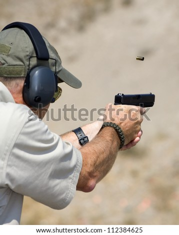 Shooter with a polymer handgun who has just taken a shot - stock photo