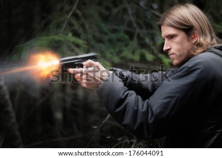 shooting a handgun and flames coming out of barrel.  - stock photo