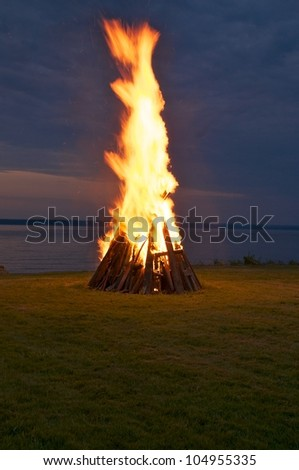 Shooting flames rise in the sky from the bonfire - stock photo