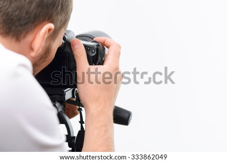 Shooting procedure. Young professional photographer uses his camera to make accurate frame.