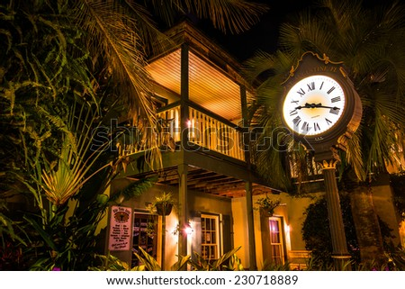 Shop and clock surrounded by palm trees and foliage at night, in St. Augustine, Florida. - stock photo