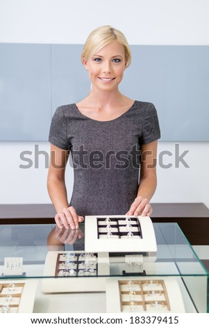Shop assistant at the window case with rings at jeweler's shop. Concept of wealth and luxurious life - stock photo