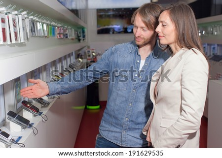 Shop assistant helping a customer choosing a smart phone  - stock photo