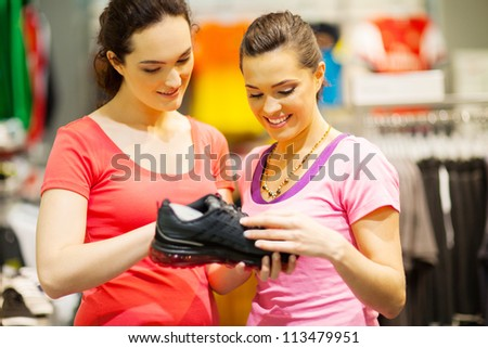 shop assistant helping customer choosing sports shoes - stock photo