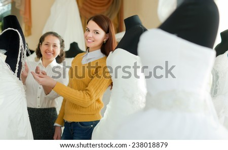Shop assistant  helps to girl chooses white bridal outfit  at shop of wedding fashion. Focus on young - stock photo