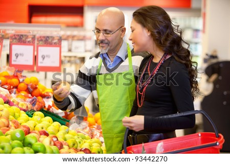 Shop assistant holding apple with customer in the supermarket