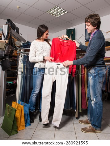 Shop assistant showing jeans and shirt to beautiful woman at the mall
