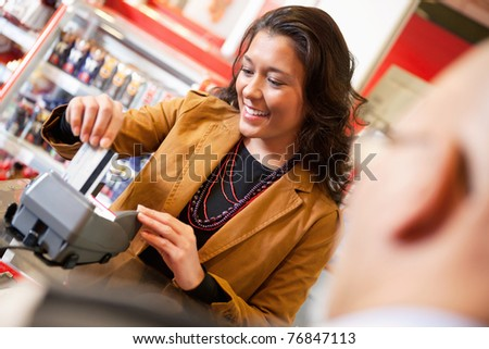 Shop assistant smiling while swiping credit card in supermarket with customer in the foreground - stock photo