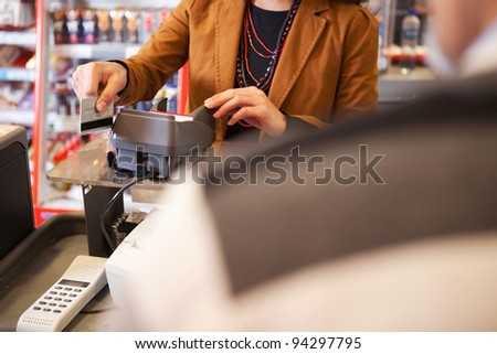 Shop assistant swiping credit card in supermarket with customer in the foreground - stock photo