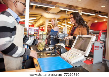 Shop assistant with customer in supermarket - stock photo