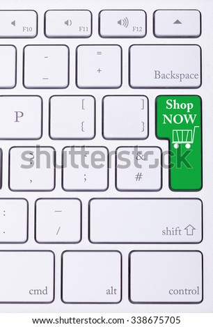 Shop now green key on aluminium keyboard. Sale and online shoping. Consumerism - stock photo