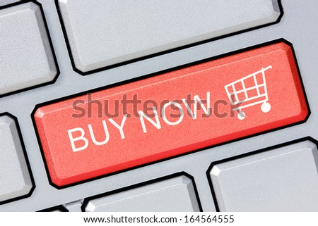 Shop online buy now business concept. Red shopping cart button on the computer keyboard  - stock photo