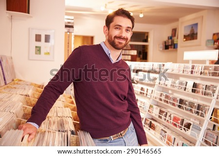 Shop owner posing in a record shop, smiling - stock photo