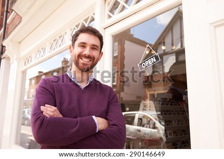Shop owner standing next to his shop - stock photo