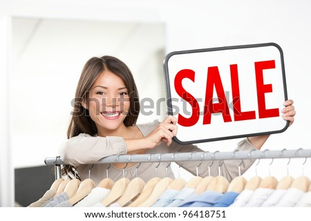 Shop owner woman sale sign. Retail store owner showing sale sign smiling happy behind clothing rack. Young female professional entrepreneur in small shop. Mixed race Chinese Asian / Caucasian woman - stock photo