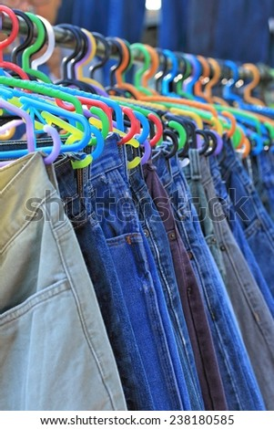 Shop pants hanging on a rack market. - stock photo