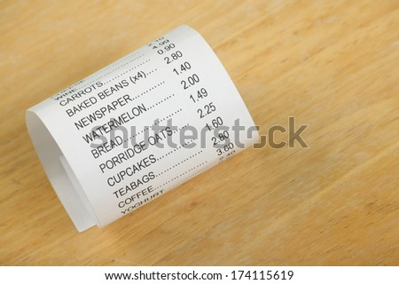 Shop receipt or till roll for food shopping curled up on a plain wood background - stock photo