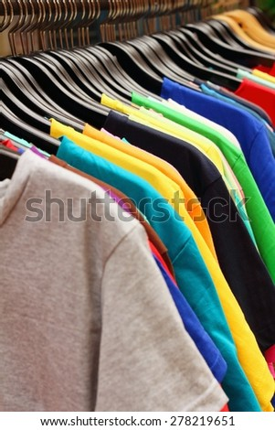 Shop shirts colorful fabric hanging on a rack. - stock photo