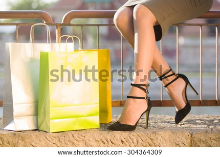Shop 'til you drop. Unrecognizable female person sitting outside next to lots of colorful shopping bags. - stock photo