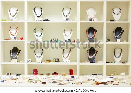 Shop window with necklaces and jewelry on display at jeweler - stock photo