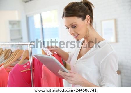Shop woman preparing summer sales in store - stock photo