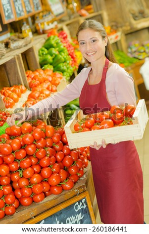 Shop worker carrying a crate of tomatoes - stock photo
