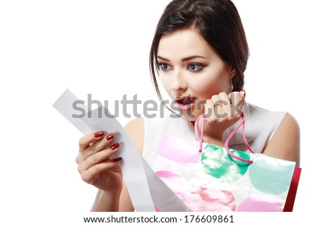 Shopaholic - Attractive brunette woman looking at her receipt - overspending