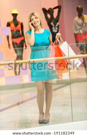 Shopaholic woman. Full length of beautiful mature woman holding shopping bags and talking on the mobile phone while standing in shopping mall