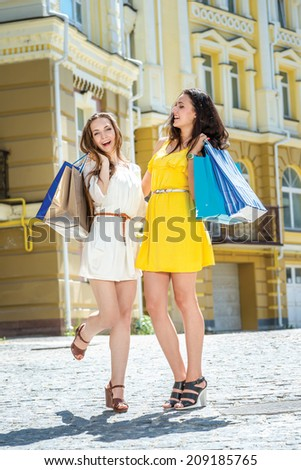 Shopaholics for a walk. Two girlfriends holding shopping bags and walk around the shops. Smiling girlfriends having fun together walking on the street