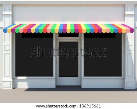 Shopfront in the sun - classic store front with colored awnings - stock photo