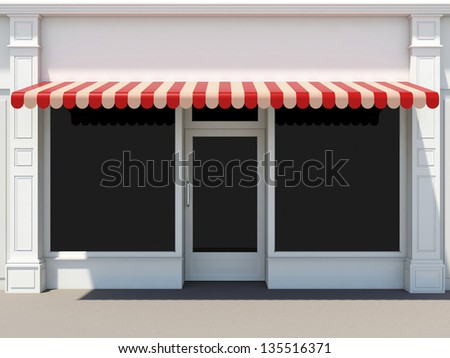 Shopfront in the sun - classic store front with red awnings - stock photo