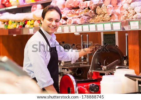 Shopkeeper cutting ham in a grocery store - stock photo