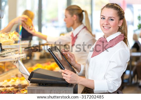 Shopkeeper or saleswoman at bakery working at cash register - stock photo