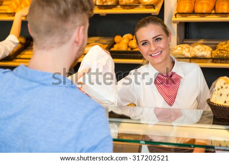 Shopkeeper or saleswoman in bakery hand bag of bread to customer
